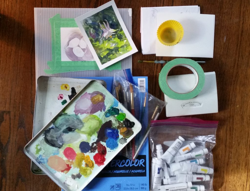 Watercolor kit: gouache and transparent paints, paper, a tin painted white inside to hold supplies and use as a palette, brushes, a silicone cup for water, a plastic support and painters tape for fixing the paper to it. Not pictured, a rag or paper towels.